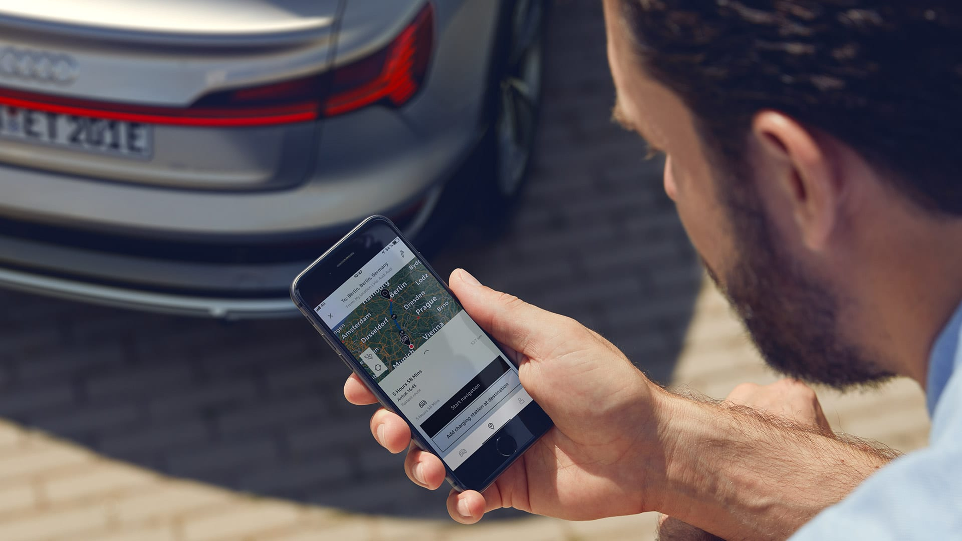 Man with smartphone in front of an Audi e-tron Sportback